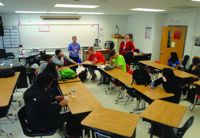 Focus is put upon students who read aloud that sit in a middle ring of desks surrounded by a larger circle.