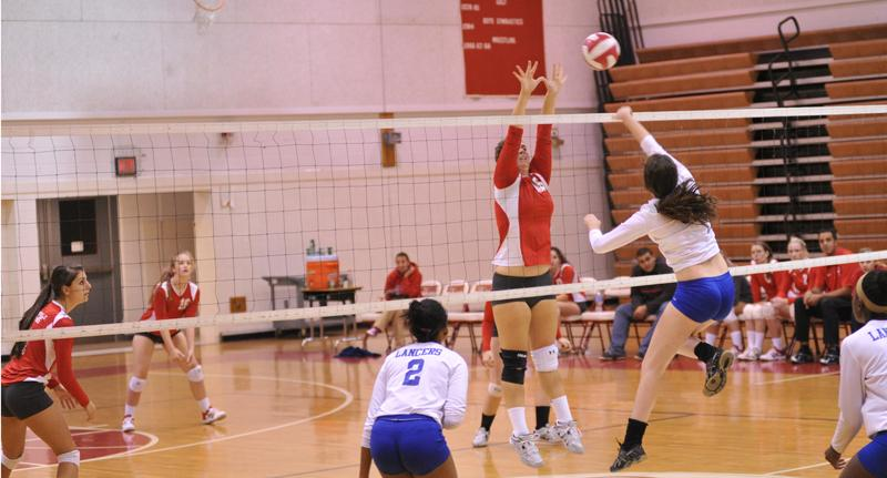 Junior Amy Reynolds jumps to block to ball and stop her opponents from scoring.