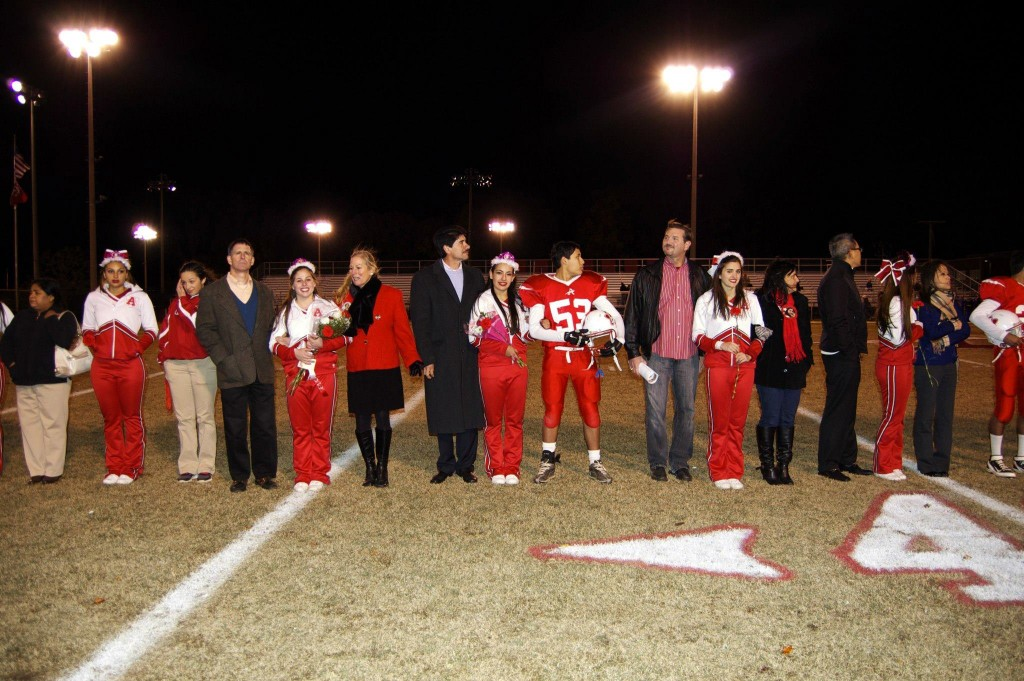 Senior football players and cheerleaders stand with their parents in celebration of their high school sports career.