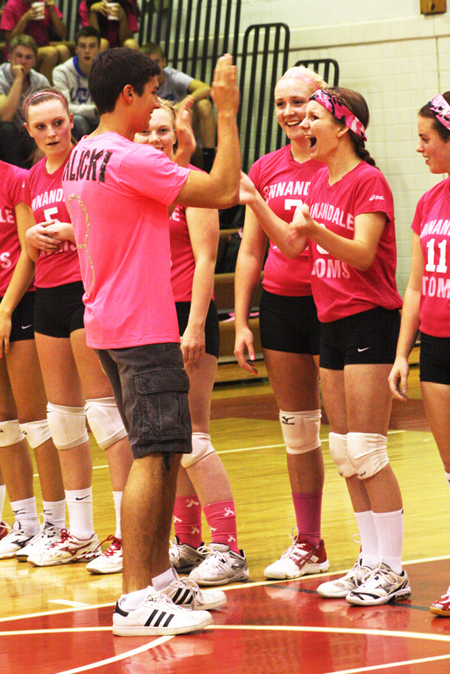 Senior Austin Chavez high fives senior Corinne Balicki during the dig pink volleyball game.  Over $600 was earned to help raise awareness for breast cancer during the month of October.