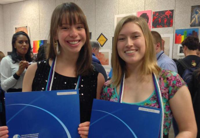 AHS alumni Danielle Turner and Carolyn Hartley of the Class of 2012 proudly hold up their official IB diplomas.