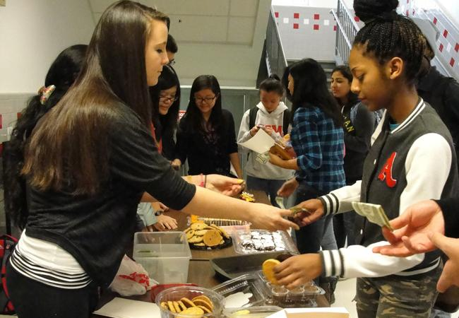 Junior Kelly Pratt collects money from a student at an SNHS bake sale.