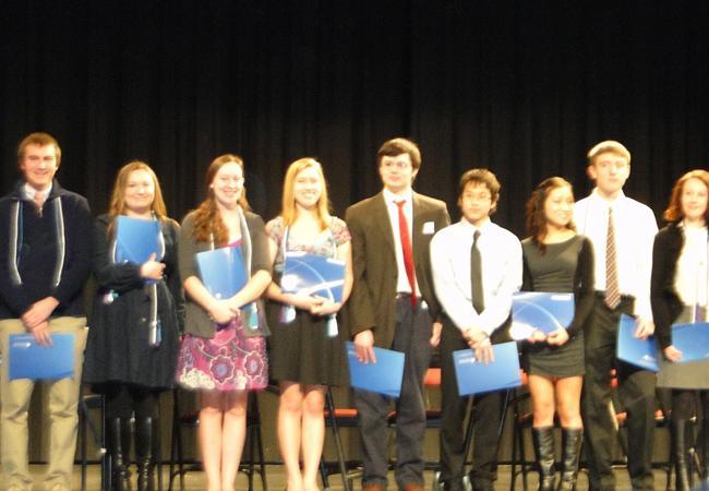 IB graduates stand as their fellow graduates receive their diplomas.