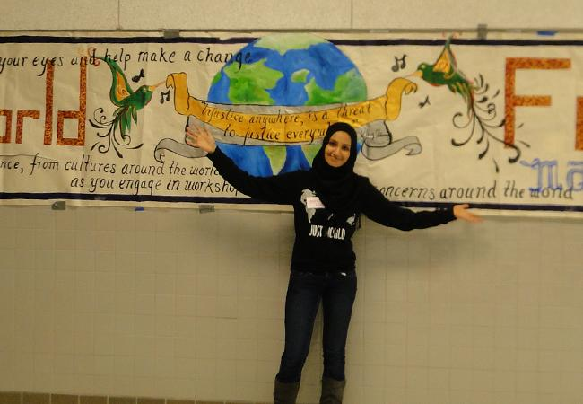 President of Just World, senior Sameen Yusuf, poses in front of the Just World banner.