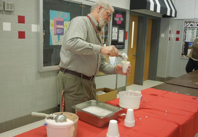 Teacher gladly serving ice cream to students who exceeded in their classees