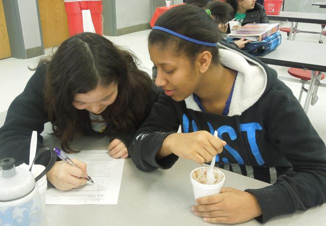 Students going over their homework while consuming ice cream