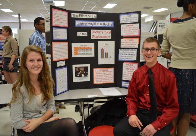 Juniors Eric Mejean and Katie McCann pose in front of their board to show their project to the judges
