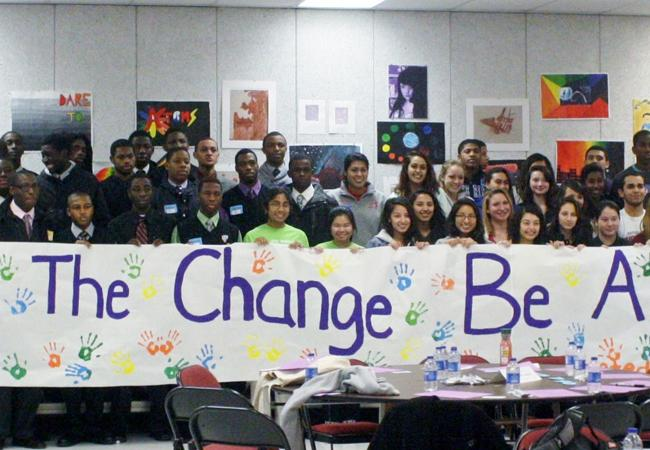 Students who participated in the conference hold a banner that reads