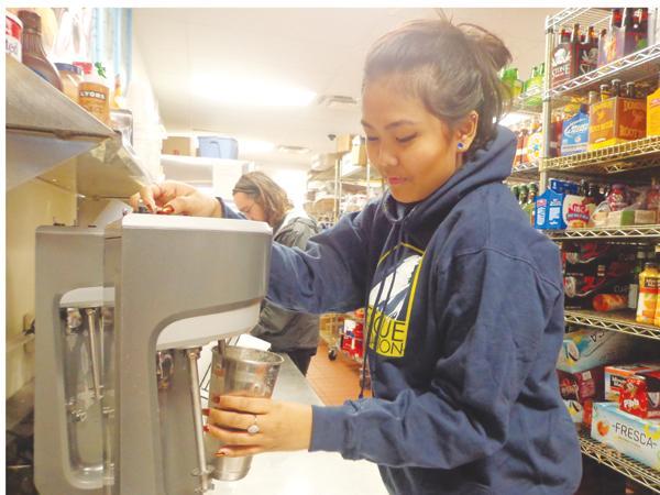Senior Visoda Heng makes a drink for a customer at Lost Dog Cafe.