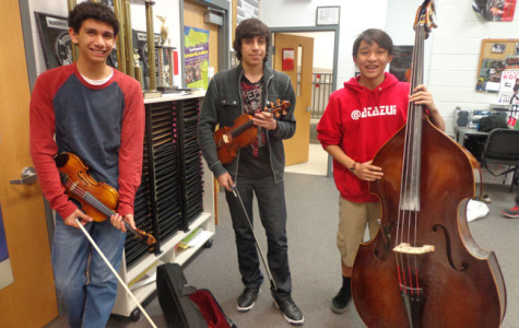 Orchestra students Ben Petruzziello, Loui Al Ayoubi and Danny Nguyen pose with their instruments.