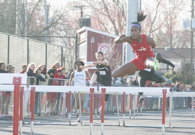 Junior Astrid Ligonde runs the 100m hurdles.