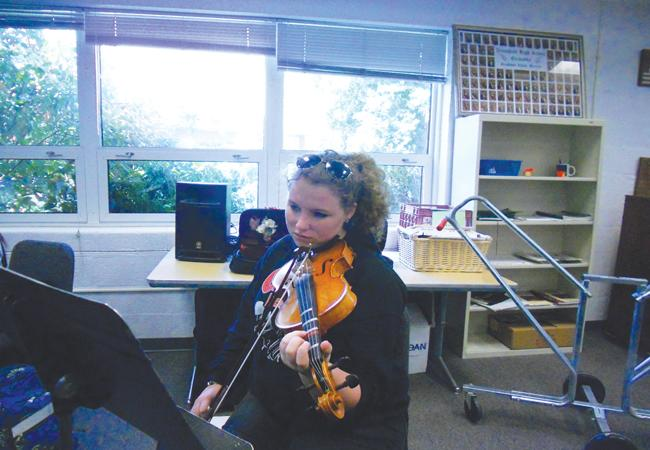 Junior Kayla Robinson practices her violin during class placement auditions.