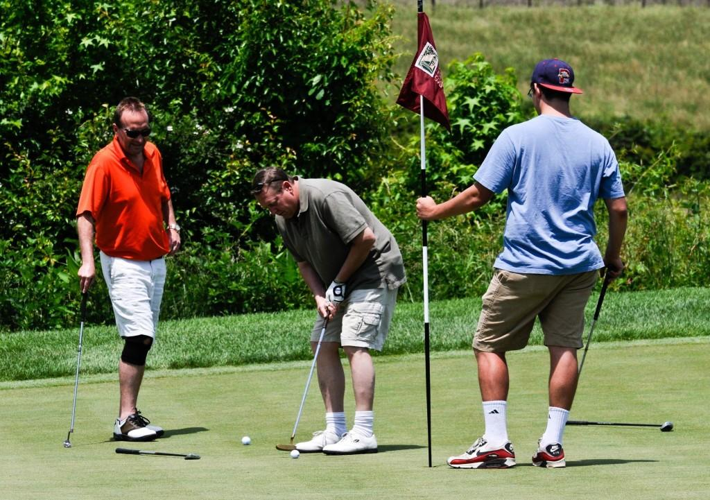 Three men participate in last year's Red and White Golf Classic.