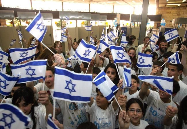Israeli children wave flags to welcome newcomers at an airport.