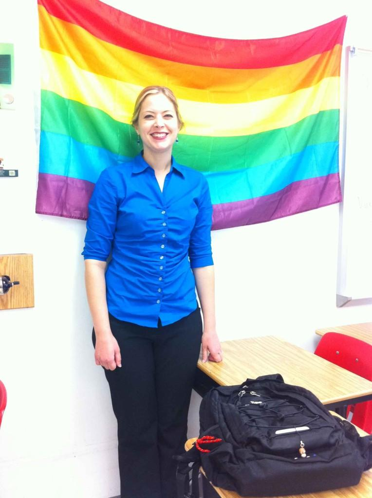 GSA sponsor Bethany Singerland stands in front of the rainbow flag, a symbol for equality.