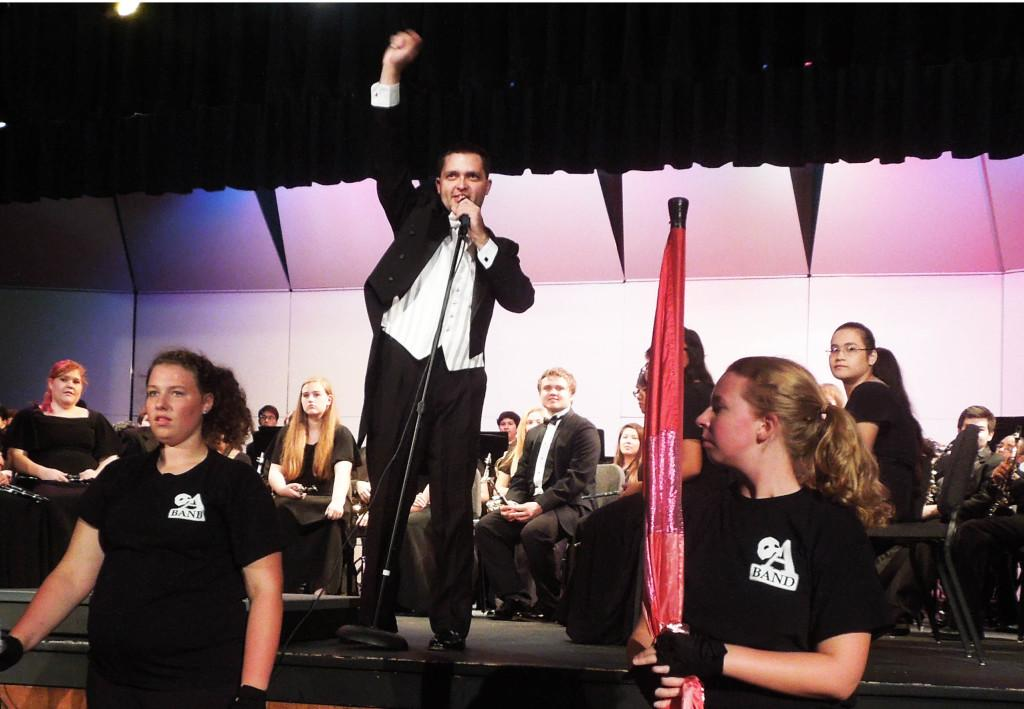 Band+director+Adam+Hilkert+addresses+the+audience+during+the+symphonic+band+and+marching+atoms%27+fall+concert.