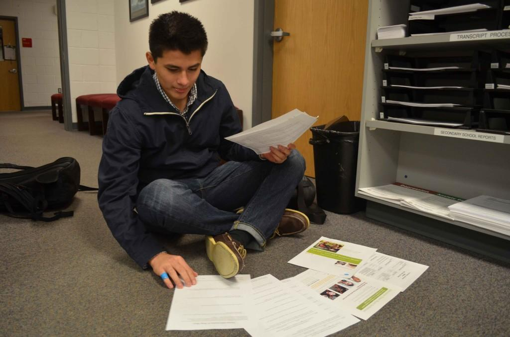 Senior Nick Torrico looks at all the papers colleges require to submit their application.