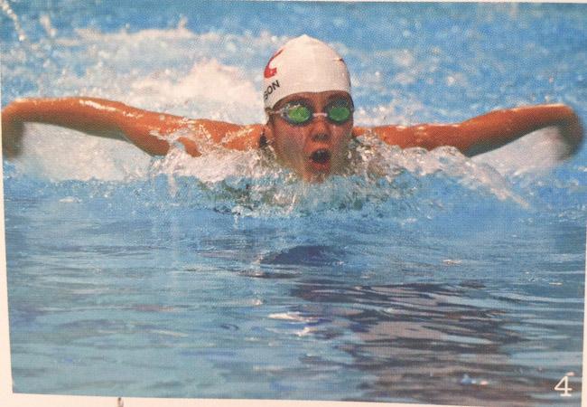 Senior+Erica+Johnson+swims+the+100+meter+butterfly+in+a+swim+meet+last+season.