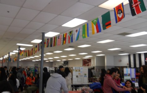 Festival goers browse exhibits under a multicolored array of national flags.