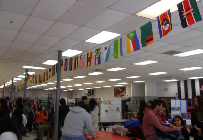 Festival+goers+browse+exhibits+under+a+multicolored+array+of+national+flags.++