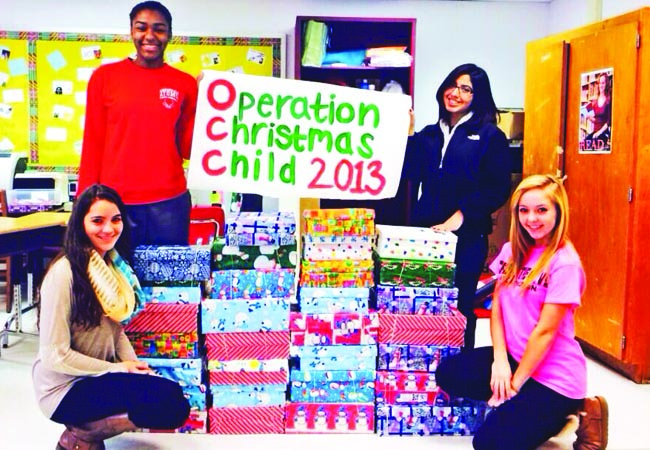 A couple of leadership students pose with the boxes filled with toys to send to kids around the world living in poverty.