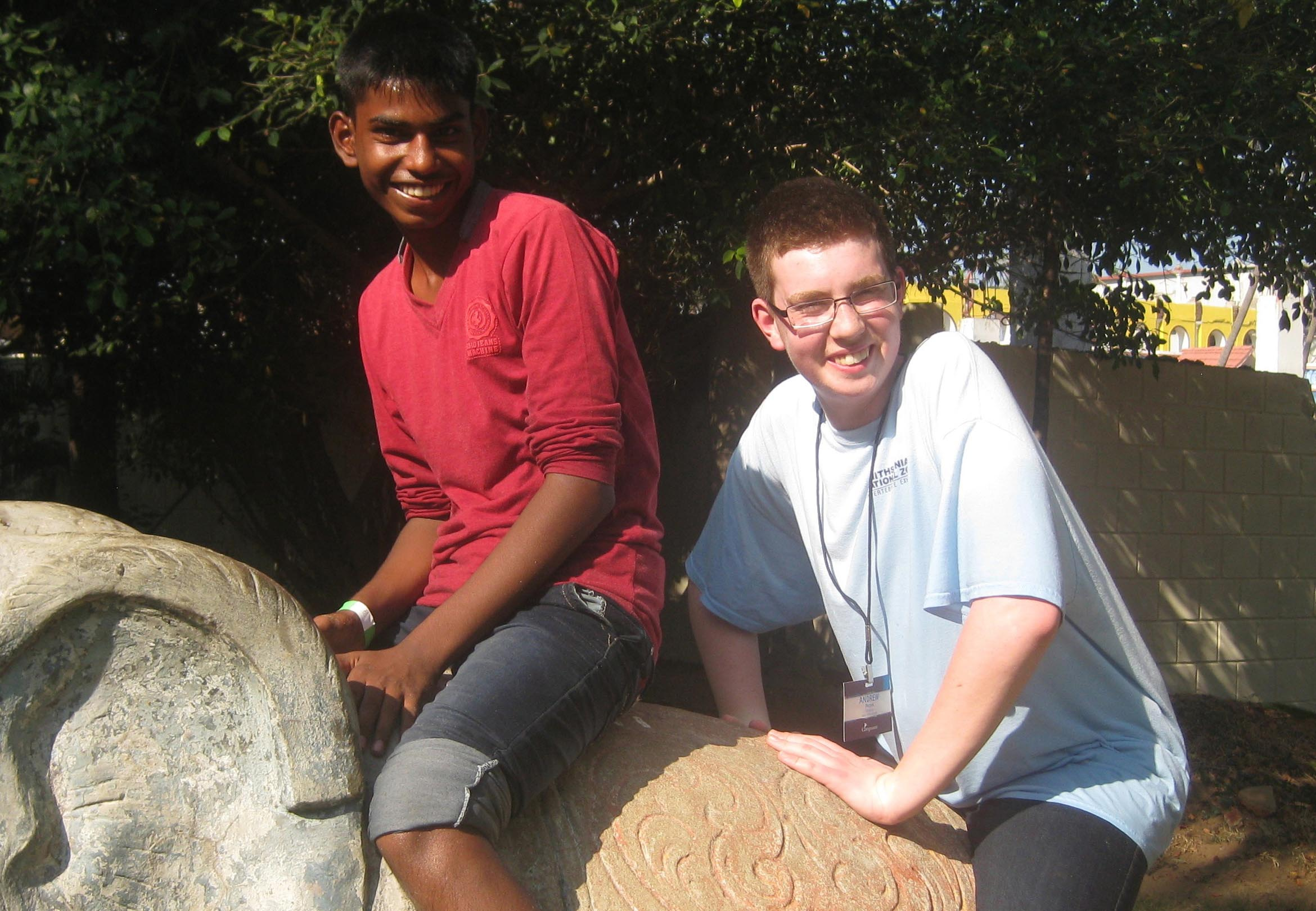 Peters and Mano sitting on a stone elephant on Fun Day