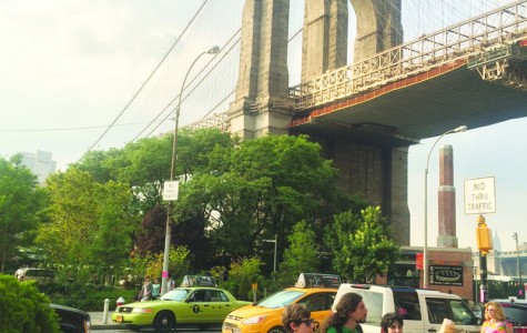 Tourists explore the artistic design of the Brooklyn Bridge, an icon and historical site in New York City.
