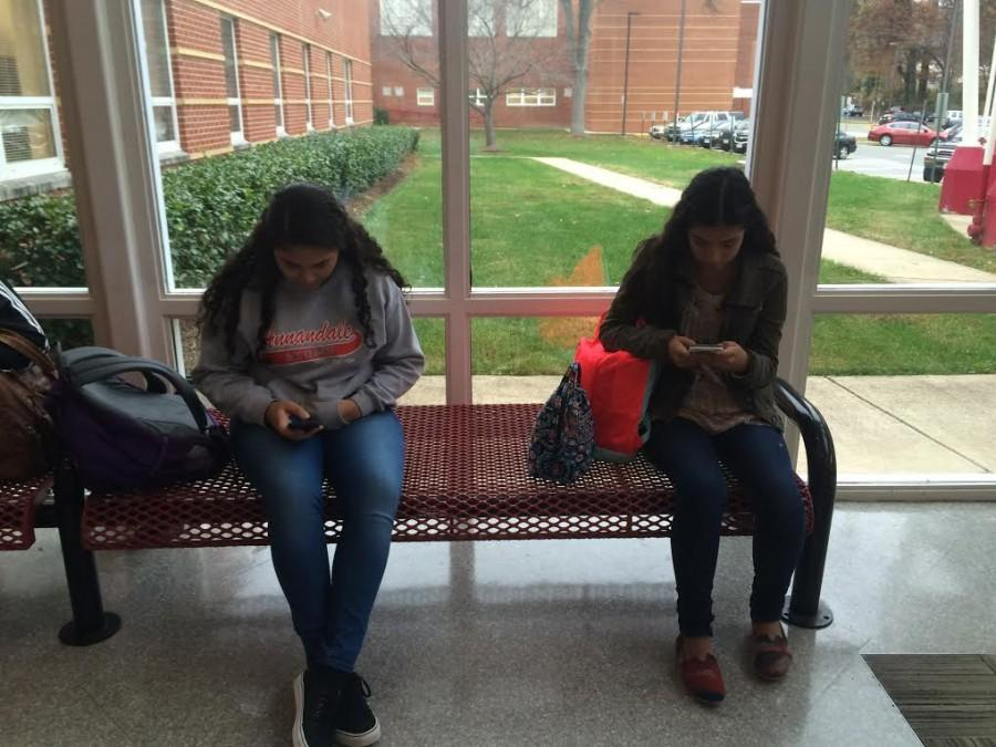 Two AHS students use their phones in the front office.