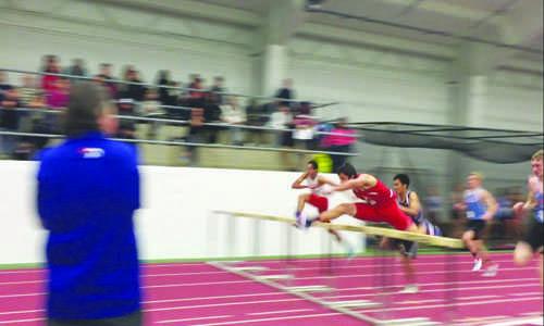 Jacob Weber runs the 50 meter hurdles at conference.