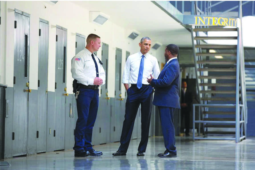 Obama speaks in front of confinement rooms at a federal prison.