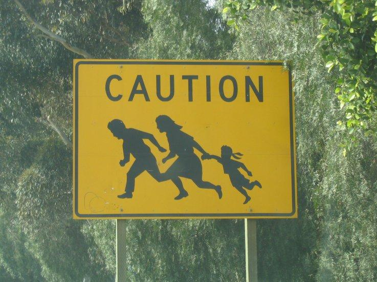 Sign near the Mexican border that warns drivers of people crossing the border into the street.