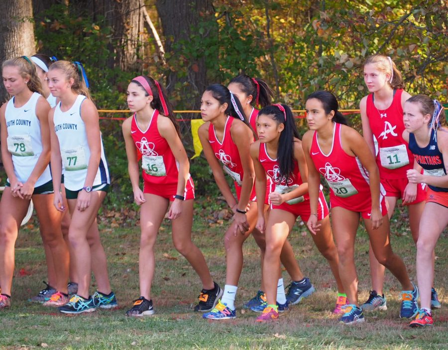 The+girls+cross+country+team+lines+up+at+the+starting+line+at+the+Patriot+Conference+Championship+Meet+on+Oct.+26.+