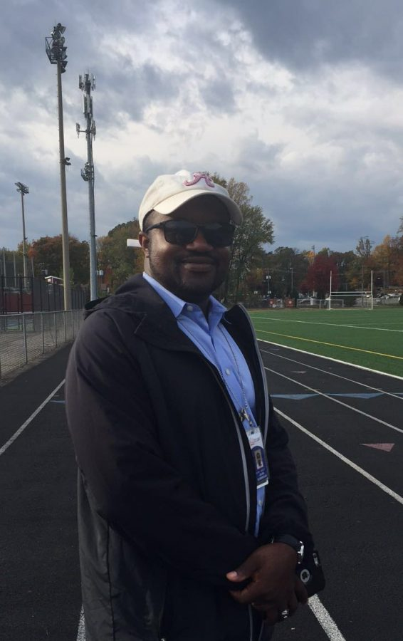 Coach Julian Scarbrough poses for a picture during track practice.
