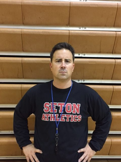 Coach Jimmy Brown poses for a picture during basketball practice.