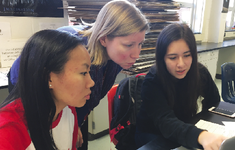 Juniors Shirley Chu and Nicole Solis ask IB Physics teacher Angel Fitzgerald about a lab. Fitzgerald regularly updates her students' gradebooks, but many teachers don't do the same.
