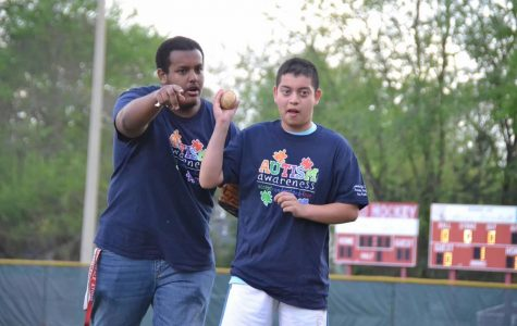Student Ricky Portillo (Right) throws out an opening ceremonial pitch on Autism Awareness Night on April 21 with Mr. Khalid Mohamed.