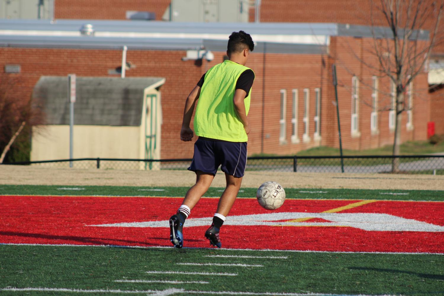 Sophomore+Andrew+Izquirdo+dribbles+the+ball+through+the+box+before+practice+on+April+18.
