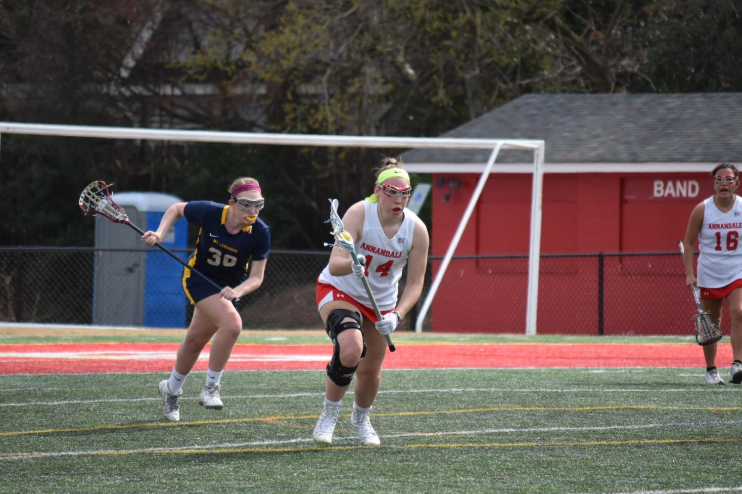 Junior Caitlyn Schwartz runs with the ball against Mt. Lebanon (PA) on March 25. The Atoms lost 11-5.