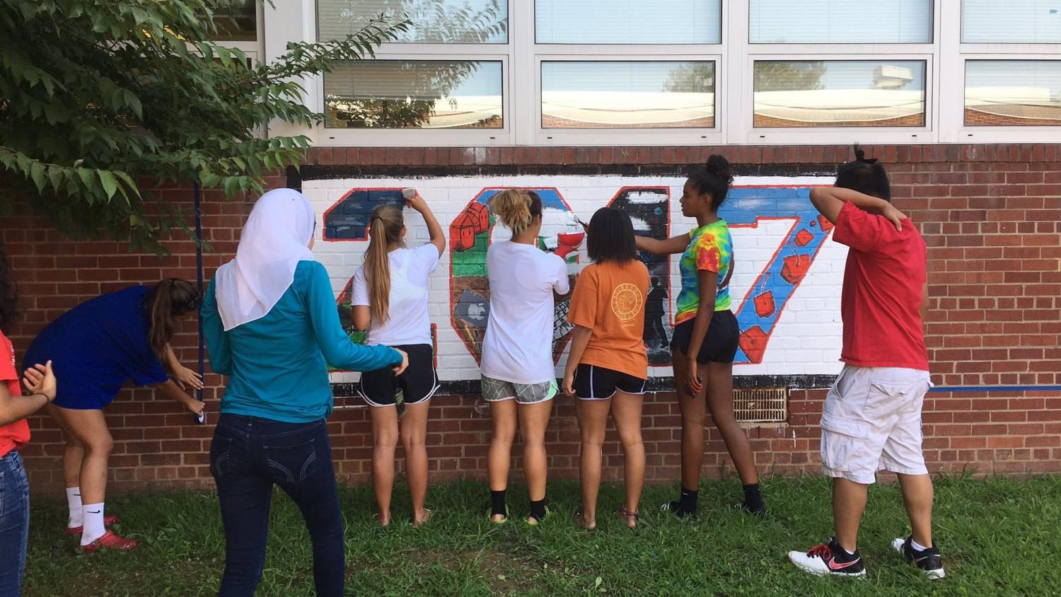 RIsing+seniors+gather+to+paint+over+last+year%27s+2017+painting+in+the+courtyard.+