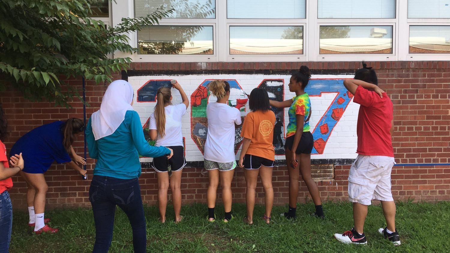RIsing seniors gather to paint over last year's 2017 painting in the courtyard.