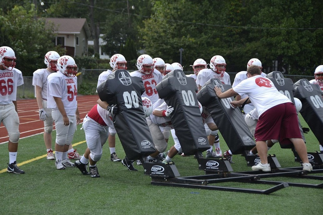 Several+players+on+the+football+team+work+together+to+push+the+heavy+sled+and+their+coach+across+the+field.+%22We+keep+each+other+focused+even+when+it%27s+hot+out+or+it%27s+raining+and+we+just+want+to+go+home.+We+fight+through+it+together%2C+as+one+team%2C+one+family%2C%22+senior+Wilfredo+Zelaya+said.+%22We+make+the+best+of+each+practice%2C+try+our+hardest%2C+and+give+each+other+confidence+for+Friday+night%27s+game.%22