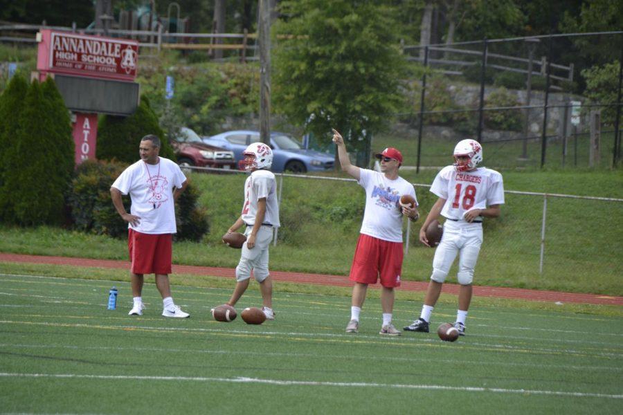 Head football coach Mike Scott and junior Matt Dinh (left) and Coach Chris Bagot and junior Devin Gill (right) work on quarterback drills.
