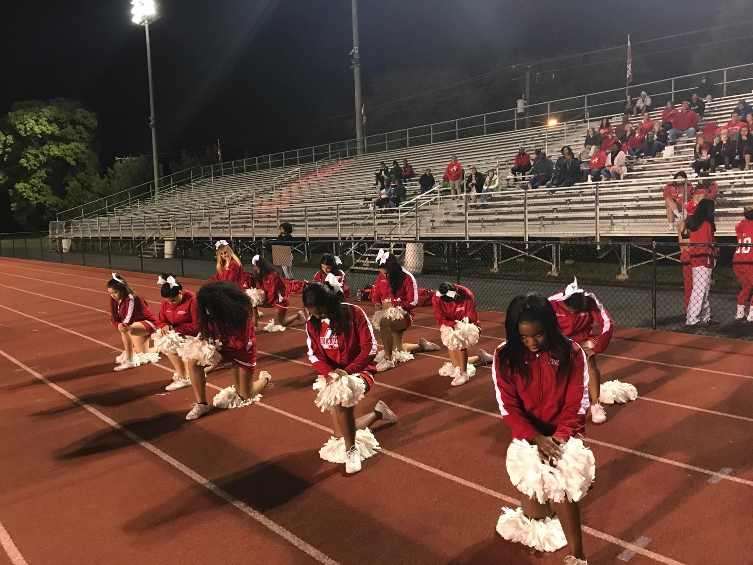 The varsity cheerleaders pose to show how some of them a knee during the national anthem.