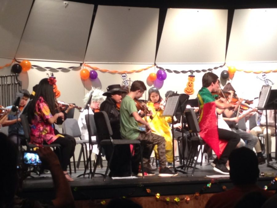 Students perform in the orchestra dressed as their Halloween characters