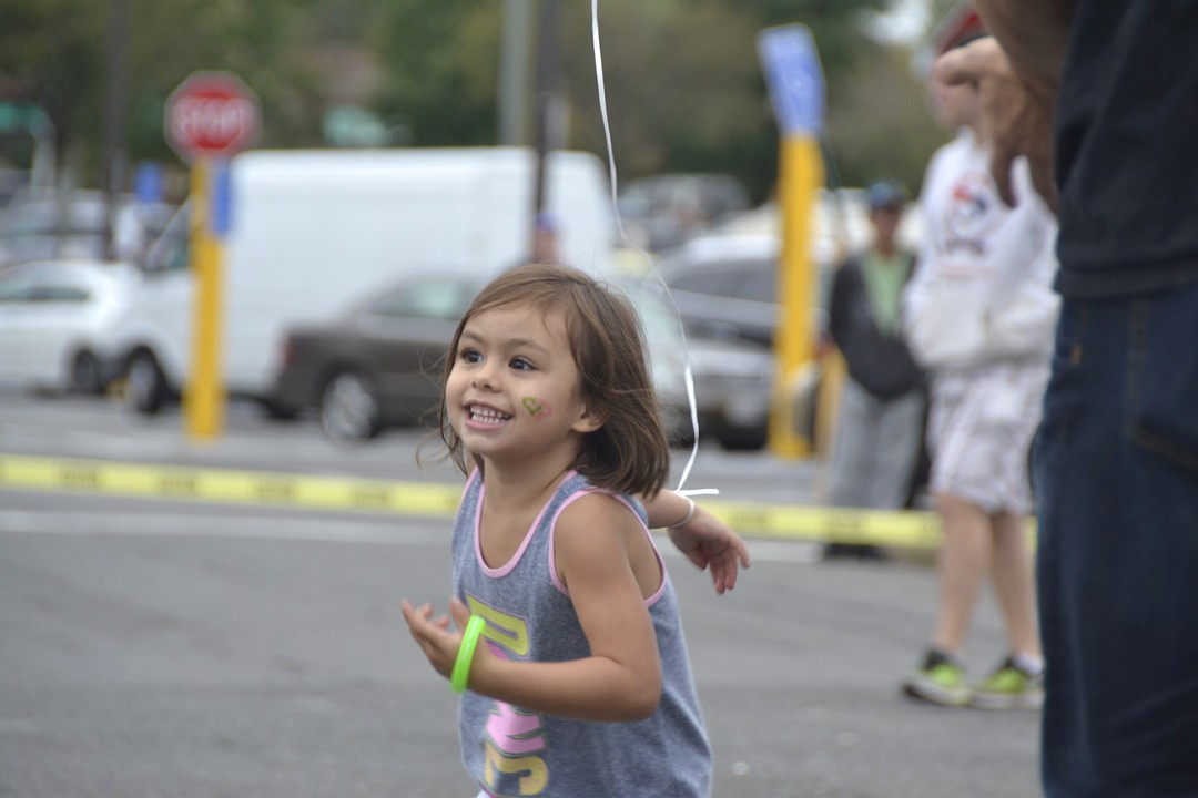 Forgetting+all+her+worries%2C+a+little+girl+joyfully+dances+around+in+circles+in+the+middle+of+the+parking+lot+for+all+to+see+and+smile+at.