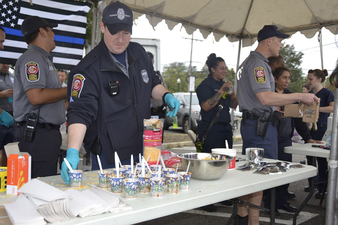 A+police+officer+sets+out+samples+of+their+chili%2C+hoping+to+win+over+the+votes+of+the+people+in+the+chili+cook-off+against+the+firefighters.