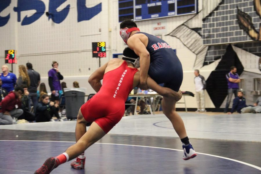 Senior Allen Kokilananda takes down an opponent at a meet against the Thomas Edison Eagles last year.