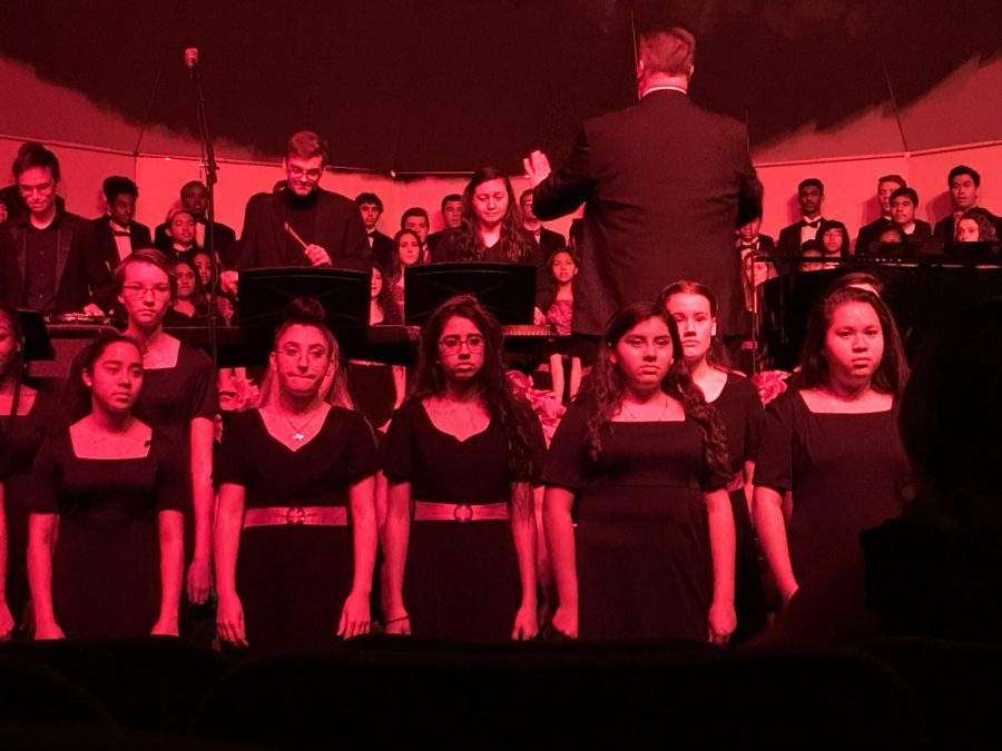 All of the choirs are singing the song Gaudete, which means rejoice in latin, with the Annandale Select Women's Ensemble at the front of the stage.