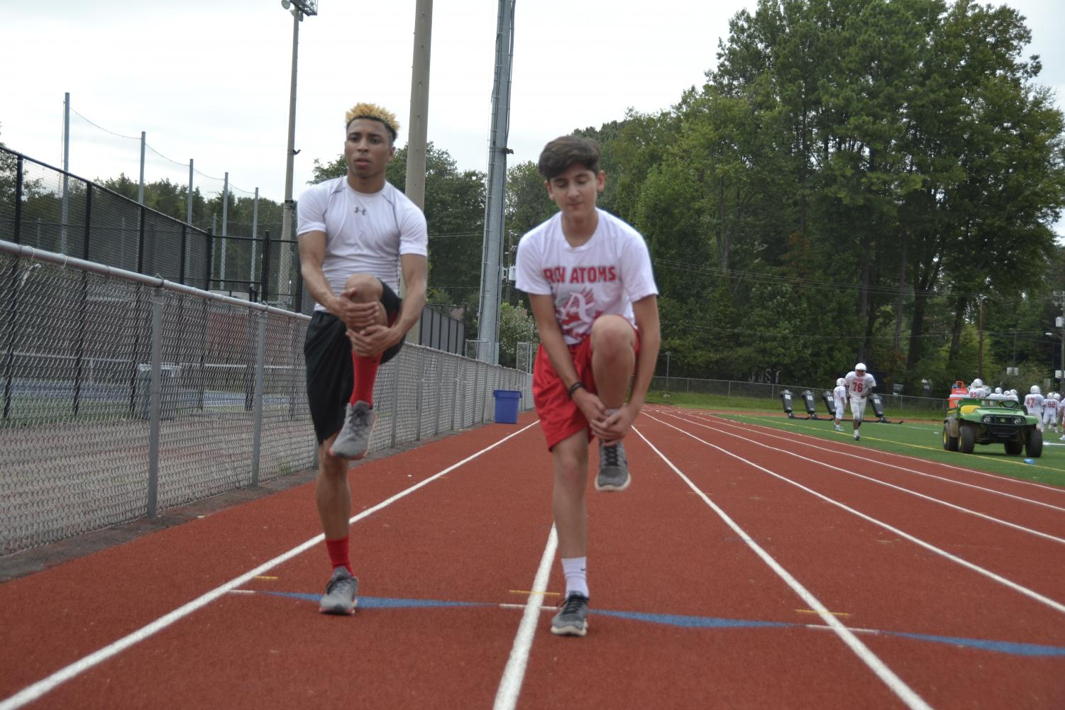 Jay Pendarvis (Left) and Tarik Darwiesh (Right) stretch in order to prepare for a run during a Green Day for track.