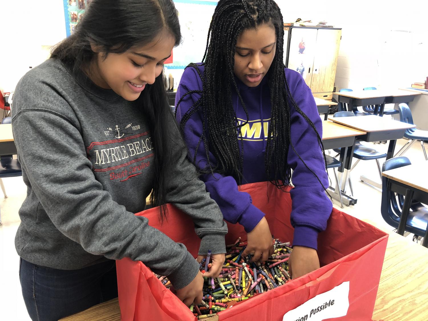 Juniors Maisha Maliha and Tiya Ayele plan details to make crayons that will be donated to the Inova hospital.